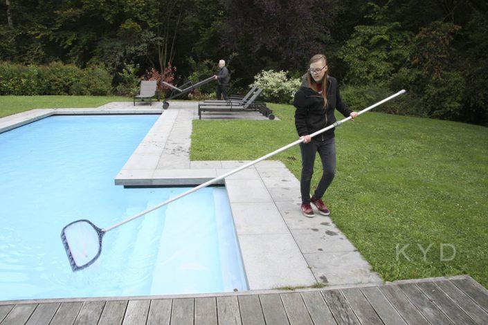 Janne ruimt het laatste blaadje uit het zwembad